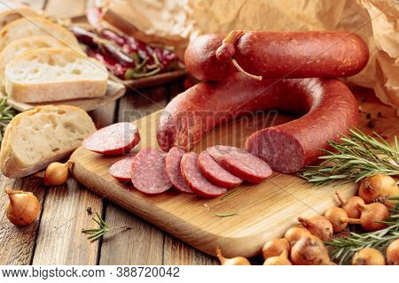 Smoked Sausage With Rosemary, Onion And Pepper. Sausage With Bread And Spices On A Old Wooden Table.