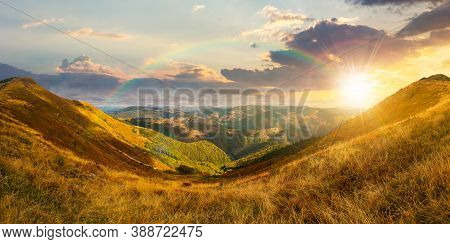 Mountain Landscape In Autumn At Sunset. Dry Colorful Grass On The Hills. Ridge Behind The Distant Va