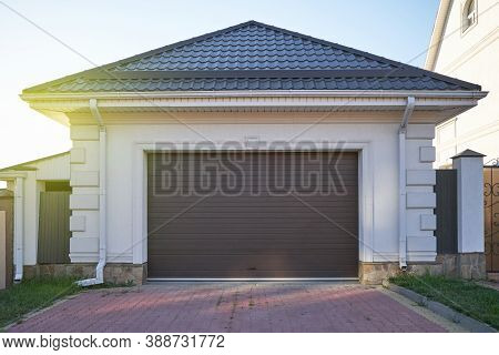 Garage With Pitched Roof And Automatic Garage Door