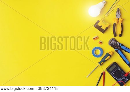 Set Of Electrician's Tools On Yellow Background. Flat Lay Composition With Electrician's Tools And S