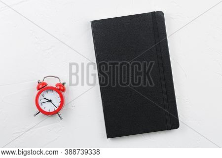 Black Leather Notepad With Red Alarm Clock On White Textured Table. Notebook Goals Plans Dreams Make