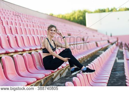 A Female Coach With Dark Hair Stands On The Red Running Track Of The Stadium