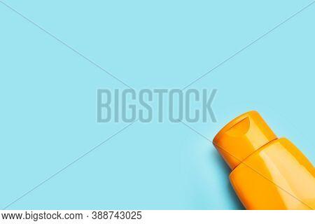 An Plastic Orange Suntan Lotion Bottle On A Light Blue Background With Copy Space