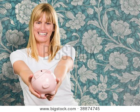 Woman Holding Piggy bank against a vintage floral background