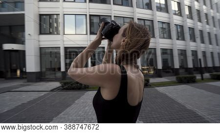 Beautiful Young Photographer Woman Takes Photos Outdoors Of A Modern Business District. Action. Came