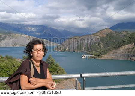 Pretty Mature Brunette Woman And A Lake On Background
