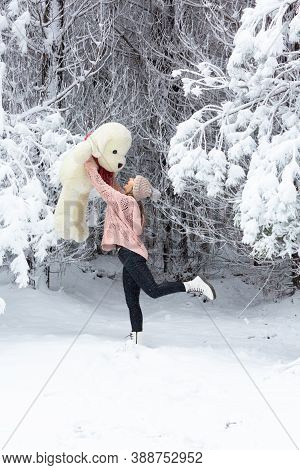 Happy Go Lucky Woman Frolicking In Snow Lifting Playfully A Large Soft Toy Above Her Head In A Snow