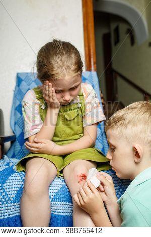 A Little Girl Hurt Her Knee, A Boy Heals Her Wound. A Scratched Knee. Brave Girl