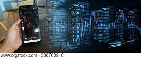 Hand Holding Smart Phone With Red Green Graph Of Stock Market Display And Ticker Board Finance And B