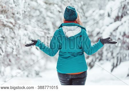 Woman Standing In Snow Among Pine Forest With Snow Falling All Around Her.