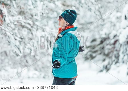 Woman Standing Out In Falling Snow In Winter Among A Forest Of Pine Trees