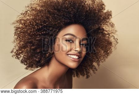 Beauty Portrait Of African American Woman With Clean Healthy Skin On Beige Background.  Smiling Beau