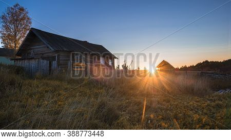 The Sun Rises At Dawn In A Village With Old Wooden Houses In Autumn.