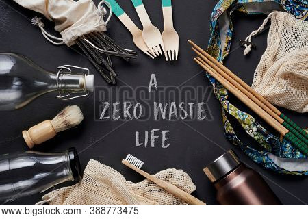a pile of no-plastic sustainable household items, such as refillable metal and glass bottles, shopping mesh bags, or reusable wooden toiletries, cutlery and chopsticks, and the text a zero waste life