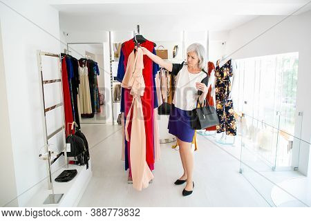 Pensive Woman Shopper Choosing Party Dress, Taking Hanger With Cloth For Trying. Woman Shopping In S