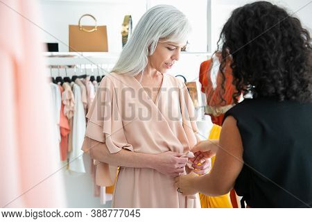 Female Shop Seller Helping Woman To Try On New Dress And Tying Waistband. Customer Choosing Clothes