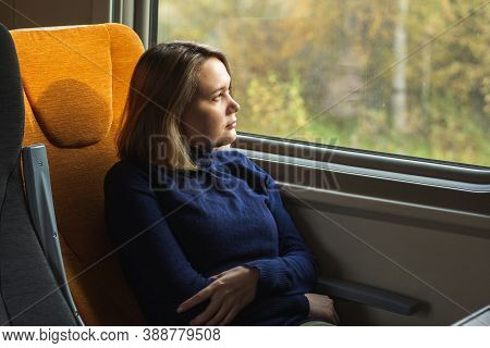 Young Woman Traveler Looking To Window Inside Of Suburban Train