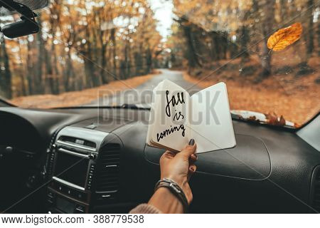 Road trip looking inside of car. Woman hand holding notebook with Fall Is Coming text over windshield. Freedom travel concept. Autumn weekend to the forest.