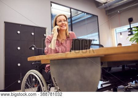 Businesswoman In Wheelchair Making Phone Call Working On Laptop In Kitchen Area Of Modern Office