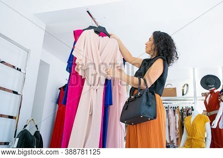 Focused Female Shopper Picking Hanger With Party Dress From Rack For Trying. Woman Choosing Cloth In