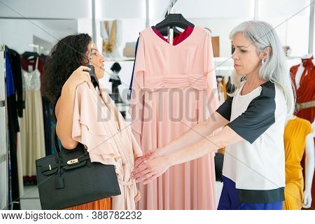 Seller Helping Customer To Choose Cloth. Woman Holding And Showing Dress With Hanger To Her Friend.