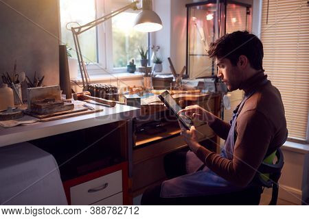 Male Jeweller Looking At Ring Design On Digital Tablet In Studio