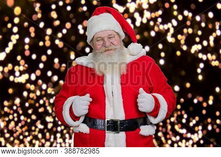 Portrait Of Bearded Smiling Santa Claus. Authentic Santa Claus In Costume And Hat Standing On New Ye