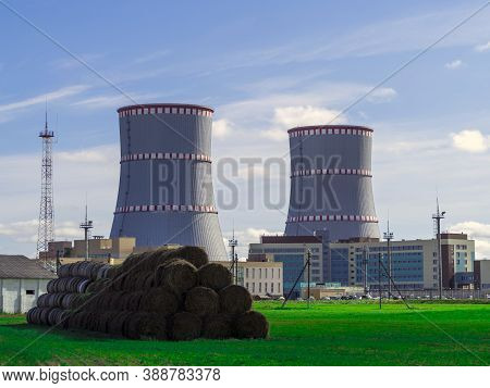 Belarusian Nuclear Power Plant. Green Field And Haystacks On The Background Of Nuclear Power Plant