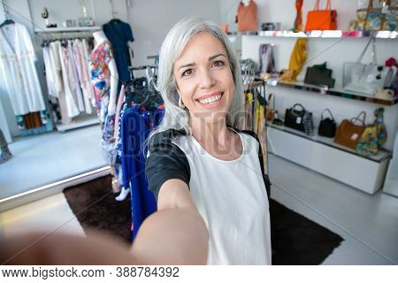 Selfie Of Cheerful Caucasian Fair Haired Woman Standing Near Rack With Dresses In Fashion Shop, Look