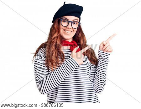 Young beautiful woman wearing french look with beret smiling and looking at the camera pointing with two hands and fingers to the side.