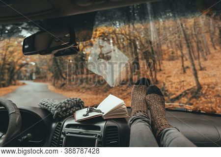 Woman feet in warm socks on car dashboard. Fall trip. Looking through windshield. Freedom travel concept. Autumn weekend.