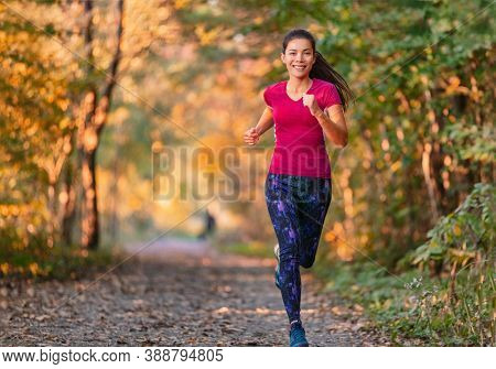 Autumn outdoor active lifestyle. Fit sport woman running in city park at sunset training cardio in nature path. Happy woman exercising outdoors in yellow leaves foliage.