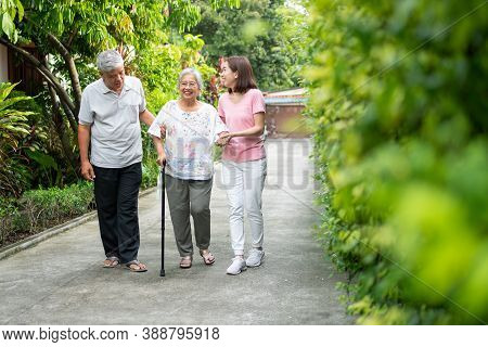 Happy Family Walking Together In The Garden. Old Elderly Using A Walking Stick To Help Walk Balance.