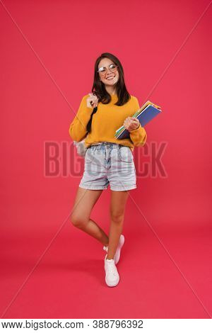 Full length of a cheerful young girl student wearing backpack, carrying textbooks standing isolated over pink background