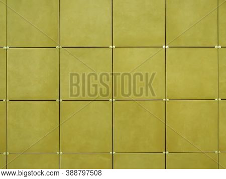 The Wall Is Covered With Yellow Square Tiles. Modern Wall Design. Exterior Decoration Of The Walls O