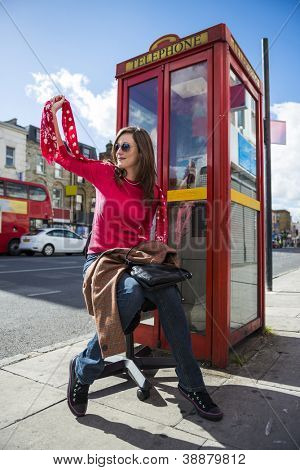 Low angle shot of fashionable young woman waving by street with red phone booth behind her