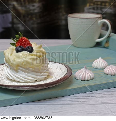 There Is A Blue Wooden Tray On The Table. On The Saucer Is A White Meringue Cake With Cream, Decorat