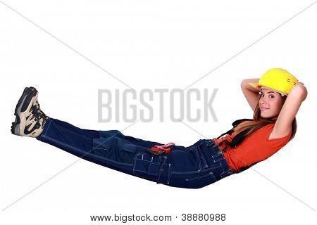 Tradeswoman lying in an invisible hammock