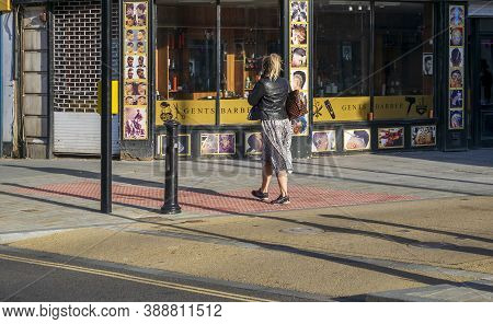 Doncaster,yorkshire, England - October 7, 2020. Girl On Her Phone Walking In Front Of The Golden Sci