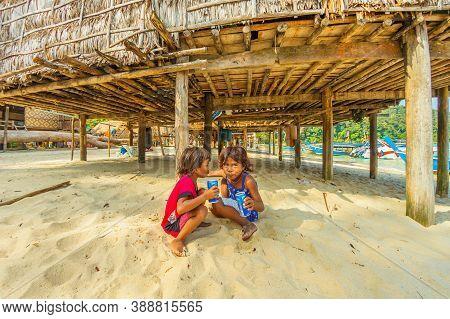 Surin Islands, Phang-nga, Thailand - January 3, 2016: Sea Gypsy Kids Sitting On Beach Drinking Pepsi