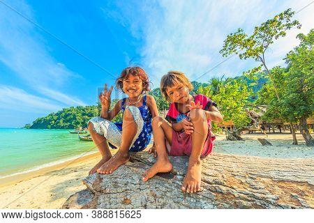 Surin Islands, Phang-nga, Thailand - January 3, 2016: Happy Children Sitting On Beach At Moken Tribe