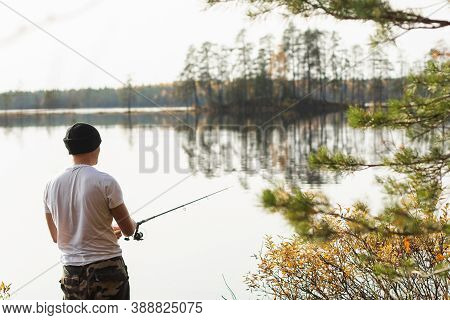 Fisherman Fishing On Spinning On Beautiful Morning Autumn Lake With Conifeur Forest Banks