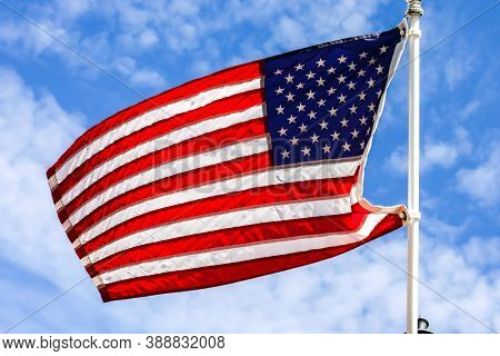 American flag with beautiful blue sky and white clouds