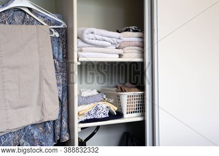 Full Closet With Clothes And Stack Of Towels In White Wooden Closet, Organization And Storage