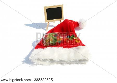 Santa Claus Hat with CBD Edible Candy. THC Infused candy on a Red Santa Hat. Isolated on white. Blank Chalk Board with room for text.