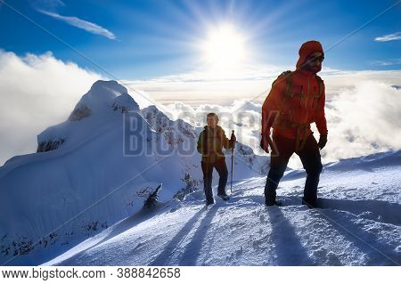 Fantasy Adventure Composite Image Of Man And Woman Mountaineering Up Snow With Mountain Peaks In Bac