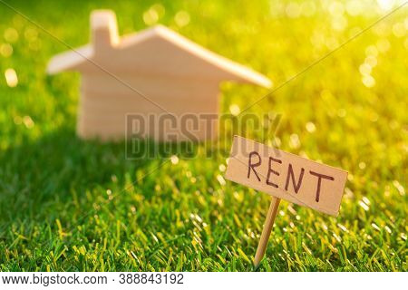 Wooden Toy House With Rent Sign On Grass