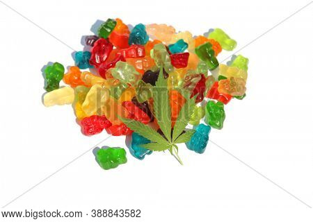 THC Edibles. Gummy Candies filled with CBD or THC. Isolated on white. Room for text. Marijuana Leaf on Candy.