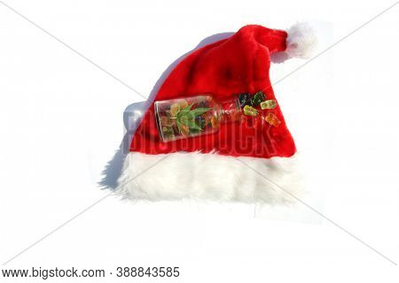 Santa Claus Hat with CBD Edible Candy. THC Infused candy on a Red Santa Hat. Isolated on white.