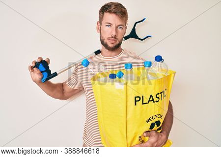 Young caucasian man holding recycling bag with plastic bottles and waste picker relaxed with serious expression on face. simple and natural looking at the camera.